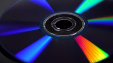 Compact disk isolated on black background. Abstract macro close up of colorful rainbow reflection from compact disc. Colorful abstract background. Rainbow on CD