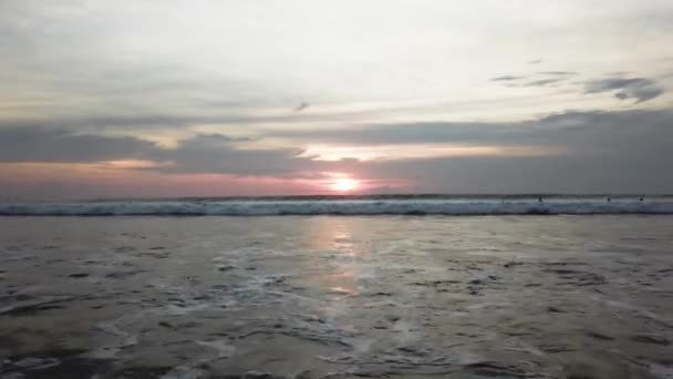 Golden sunset on the ocean shore and sand. Video. Ocean waves on the shore on sunset