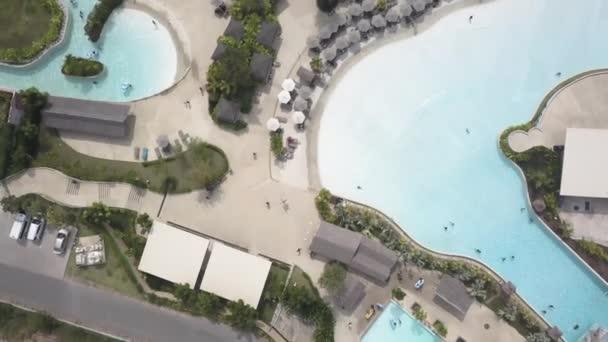 Vista superiore delle piscine alla spiaggia tropicale in hotel di lusso. Video. Vista superiore di un tourist hotel con piscina