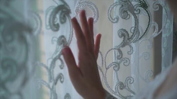 Hand öffnet Vorhang am Fenster Holzhaus Haus. Clip. Helles Sonnenlicht durchscheint. Schönen verschneiten Wintermorgen Licht hinter dem Chalet-Fenster