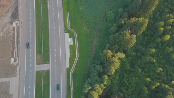 Dálnice silnice mezi stromy. Klip. Letecký pohled na Truck jízdy na silnici highway na zelený les. Asfaltová silnice v krásném lese