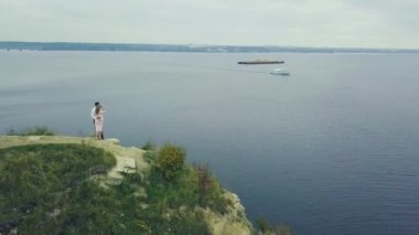 Couple standing against amazing nature view. Clip. Couple is standing on a mountain cliff by the lake. Beauty world. The feeling of complete freedom. Aerial