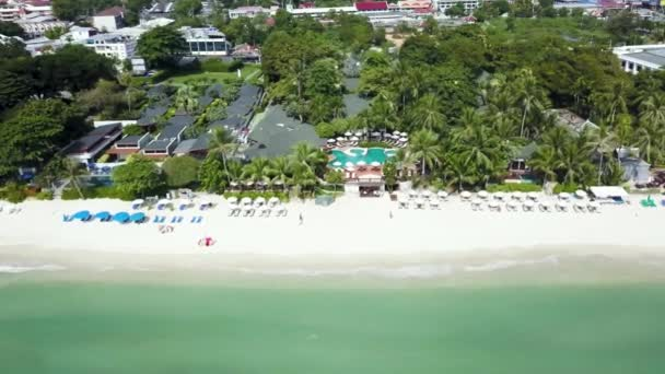 Letecký pohled na luxusní dům na pláži s palmami a bazénem. Pohled shora domů na palm beach, bazén a loď poblíž dřevěné molo. Letecký pohled shora na šířku