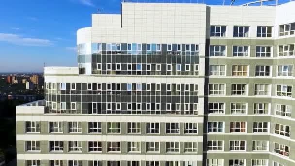 Letecký pohled na bytový dům nebo bytový dům s odraz slunce. Klip. Velké bílé moderní bytový dům pohled z oblohy