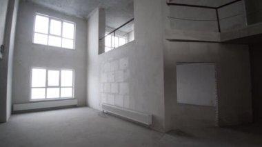 Dokončovací práce na zrekonstruovaném bytě. Klip. Omítnuté zdi, tapetování, malovaný strop, srovnal podlahu. Instalace elektrických rozvodů. Prázdné světlém interiéru. Rekonstrukce bytu