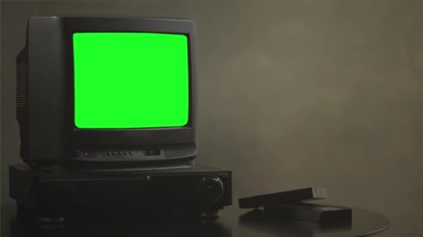 Vintage televize na dřevo stůl s chroma key zelená obrazovka. Stará Tv s zeleným plátnem. Poblíž televizoru jsou filmové kazety