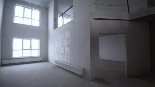Rekonstrukce interiéru. Klip. Prázdná bílá stěna s oknem a betonové podlahy