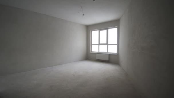 Rekonstrukce interiéru. Klip. Prázdná bílá stěna s oknem a betonové podlahy.