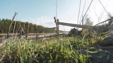 Wooden fence and green grass with sun reflection and lake with blue sky background. Video. View of a farm gate leading into countryside. Countryside landscape