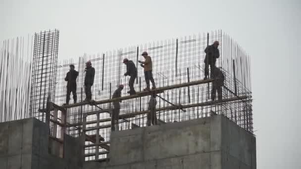 Stavitelé budování bílé zdi na staveništi. Klip. Panorama zastřelil