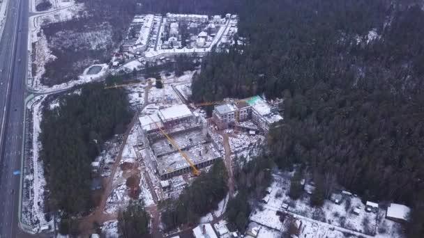 Pohled shora vidět staveniště železobetonové výškové budovy. Klip. Pohled shora stavební konstrukce s věžové jeřáby