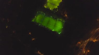 Footbal soccer field night aerial. Clip. Long exposure birds eye view of green footbal court. Top view of the football field at night