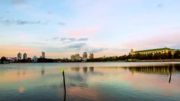 Malebné panoráma města projeví na jezeře při západu slunce. Video. Městská noční scéna. Panoráma města pobřeží jezera s pozadím budovy a západ slunce