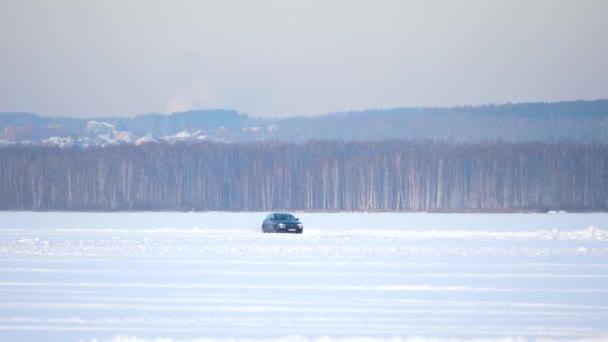Jízda v zimě. Modré auto jednotky ledové dráhy na sněhu se jezero na zimní. Sportovní závodní auto na trati v zimě sněhu. Řídit závodní auto na zasněžené vozovce