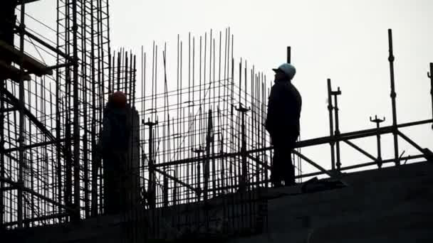Silhouette man engineer construction site construction worker on construction site. Clip. Silhouette of a worker in a helmet at a construction site