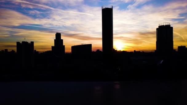 Letecký pohled na krásné barevné Dramatické nebe nad siluetou města. Klip. Siluety města při západu slunce s mrakodrapy pozadím. Západ slunce v městě s obchodními centry pozadí
