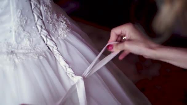 družička vázání mašlí na svatební šaty. Klip. Družička dělá luk uzel na zadní straně nevěsty svatební šaty. Nevěsta má na sobě svatební šaty