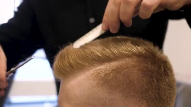 Közelről férfi haj vágás ollóval a szépségszalonban. Fő darabok haj és szakáll férfi a fodrászatban, fodrászat frizura teszi egy fiatalember. Az ember a fodrász szalonban közelről