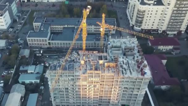 Busy Construction Site and Construction Equipment Aerial. Real construction site industrial skyscraper building structure with labor and workers working in high risk form aerial view. Aerial view