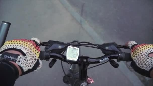 Jízda na horském kole přes uličky města. Muž v sportovní, zdravého životního stylu. First person pohled, volant