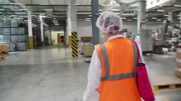 Sledujte záběry z tovární dělník v přilbou, která se prochází průmyslová zařízení. Klip. Následující snímek průmyslové zaměstnankyně v přilbu procházel těžkého průmyslu