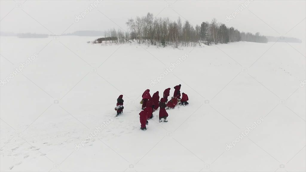 Meditating monks in the forest in winter. Footage. Hooded people follow each other in Snowy Woods like monks who seek enlightenment