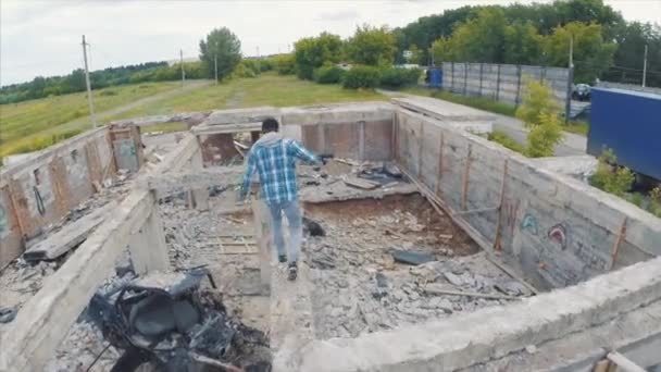 Young man walks through the ruins. Clip. A man runs through the abandoned ruins, aerial view
