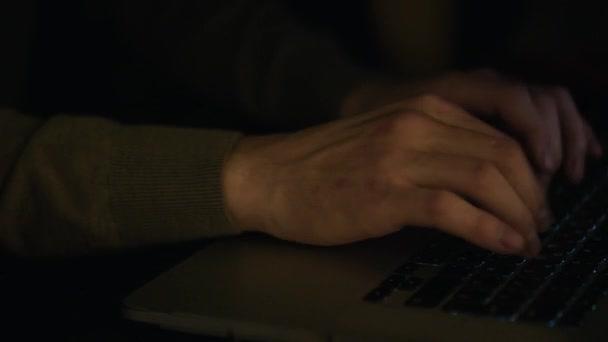 Zblízka se mužských rukou textu nebo programový kód v počítači v přirozené osvětlení pozdě večer. V UK