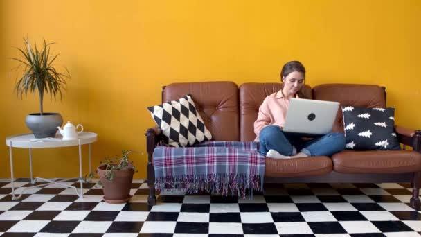 junge attraktive Frau, die hart am Laptop im Wohnzimmer arbeitet. Archivmaterial. schöne junge Frau tippt auf Laptop sitzt auf Sofa im Wohnzimmer. Freiberufler arbeiten zu Hause am Laptop
