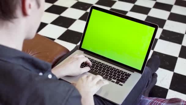 Közelkép egy fiatalemberről, aki a laptopnál gépel, zöld scree-vel. Készletfelvétel. Fiatal programozó vagy szabadúszó dolgozik laptop zöld képernyő