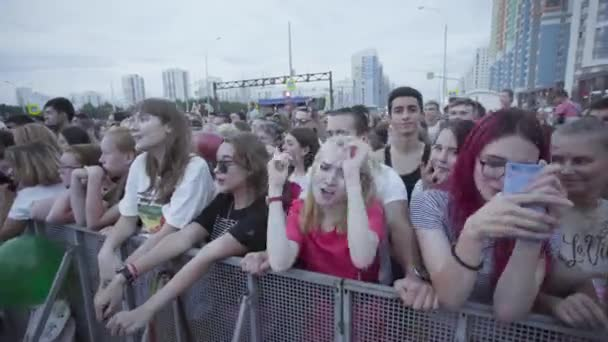 Russia - Moscow, 07.07.2019: Crowd at an outdoor concert having fun. Art. Young blonde girl singing and dancing with other people during the show.