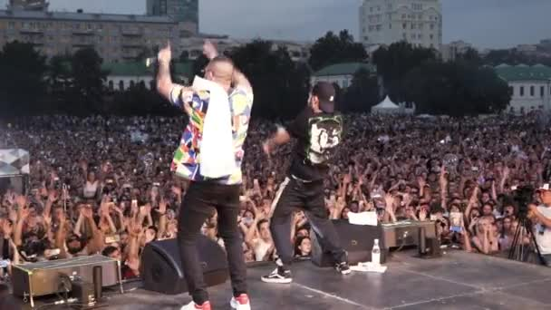 Spain - Barcelona, 07.09.2019: rear view of two rappers shaking hands on the stage during the concert. Action. Two hip-hop artists performing live at the festival.
