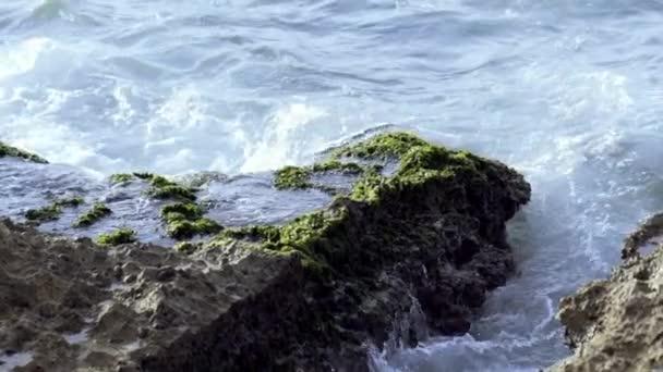 Kis hullámok csapódnak és fröcskölnek a tengerpartra. Felvétel. A hullámok kőnek ütköznek. Tengeri hullámok kis sziklákon