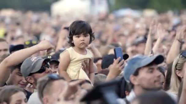 Jekatěrinburg, Rusko-srpen, 2019: Dav fanoušků na koncertě se zdviženýma rukama a dívkou. Akce. Malý vějíř se drží nad celým davem s rukama zvednutýma na koncertě odpoledne