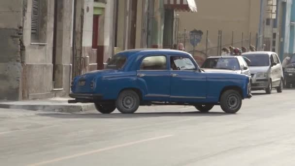 Havana, Cuba - May, 2019: Cubans pass colorful classic American car. Action. Life on the streets of Havana passing vintage cars
