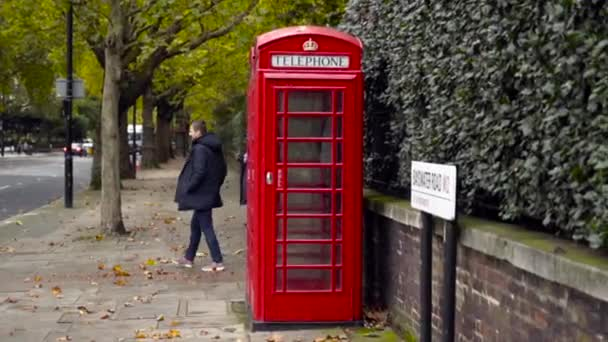 London, Britain-September, 2019: Red telephone booth on street with trees and people. Action. Red public telephone booth on streets is English tourist attraction