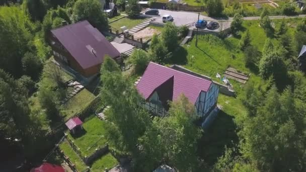 Aerial view of residential neighborhood and houses in summer village. Clip. Top view of bright pink roofs of cottages built in ecological area.
