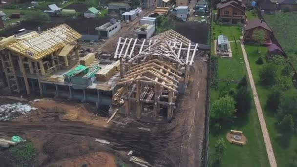 New home wooden construction from above in countryside area. Clip. Aerial view of summer green village and a new wooden log house.