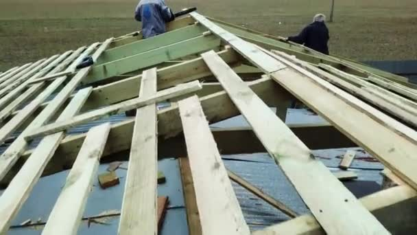 Tesaři stavějící střechu domu na staveništi na zeleném trávníku a malé vesničce na pozadí. Záběry ze skladu. Dělníci na nedokončené dřevěné střeše.