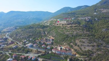 Flying over sunny town Alanya in Turkey located by the Mediterranean sea. Art. Aerial view of the mountain slope covered by houses and trees.