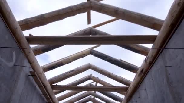 Dolní pohled na dřevěný krovový systém, výstavba střechy domu na kalném pozadí oblohy. Klip. Nedokončená střecha a dvě betonové stěny a staveniště.