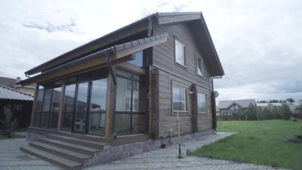 Schönes modernes Haus mit Panoramafenstern, gebaut in ökologischem Gebiet. Archivmaterial. das Ferienhaus auf der grünen Wiese vor bewölktem Himmel.