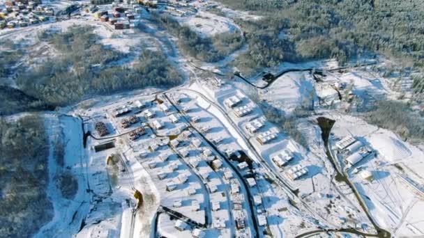 Letecká zimní krajina, malé městečko na severu Ruska se zasněženými stromy po silném sněžení. Pohyb. Létání nad borovicemi lesa a malých domků.