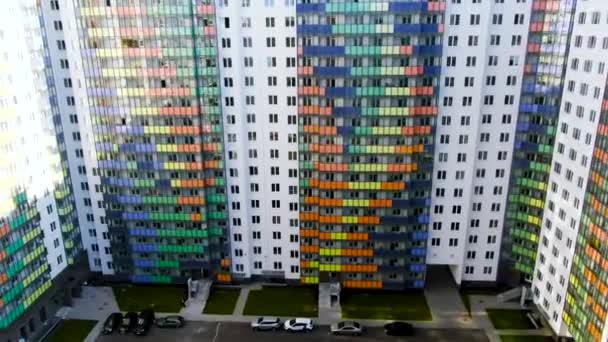 Nagy színes apartman épületek lakótelepen zöld gyeppel a bejárati ajtók közelében. Indítvány. Gyönyörű felhőkarcolók a modern város területén.