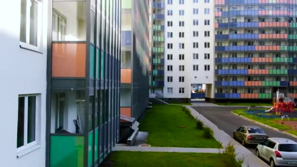 Colorful playground inside the yard surrounded by new residential houses. Motion. Bright building with colorful balconies and green lawn.