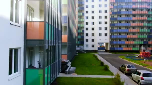 Barevné hřiště uvnitř dvora obklopené novými obytnými domy. Pohyb. Světlá budova s barevnými balkony a zeleným trávníkem.