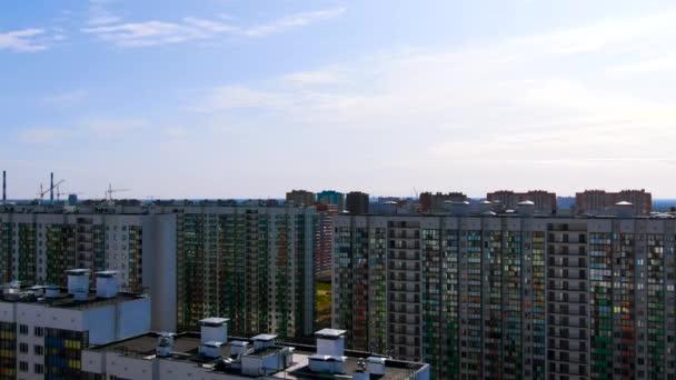 Weiße Häuserzeilen mit bunt gestreiften Fassaden vor dem blauen Himmel mit Wolken. Bewegung. Luftaufnahme von Wohngebäuden.