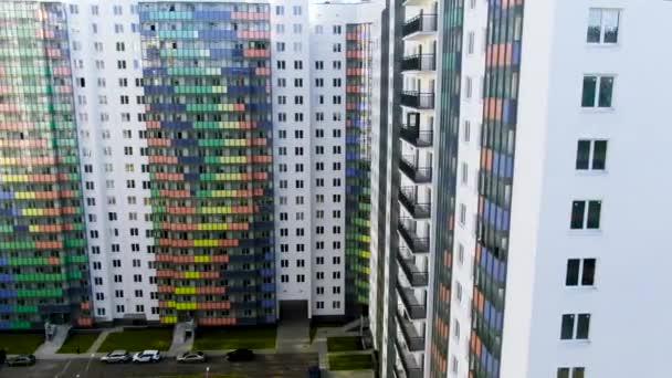 Luftaufnahme des neuen bunten Gebäudes in der Stadt mit hellen Streifen an der Fassade. Bewegung. Äußere des Wohnhochhauses und der Innenhof.