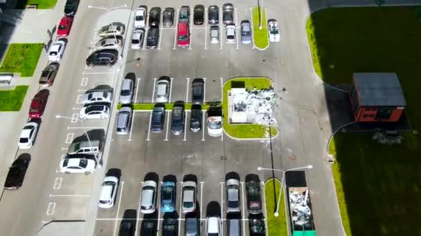 Luftaufnahme von Parkplätzen mit vielen Autos in der Nähe von grünem Rasen. Bewegung. Blick von oben auf den Parkplatz mit Betonpflaster an einem sonnigen Sommertag.