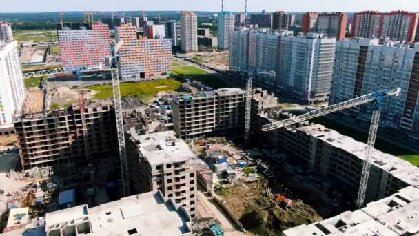 Aerial view of apartment buildings at construction site with four working cranes. Motion. The process of developing of new city district and houses under construction.